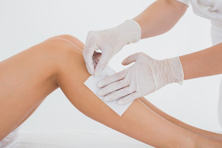 Mid section of therapist waxing womans leg at spa center photo