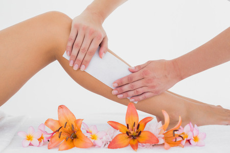 day spa: Mid section of therapist waxing womans leg at spa center