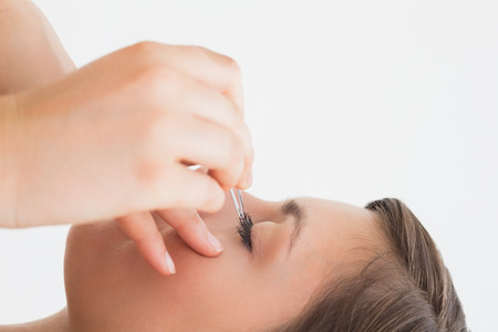 Close-up side view of hand plucking eyelashes over white background photo