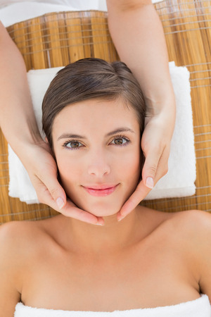 Close up of an attractive young woman receiving facial massage at spa center photo