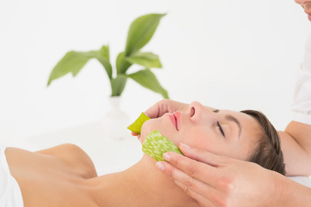 Side view of an attractive young woman receiving aloe vera massage at spa center