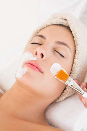 Close-up of an attractive young woman receiving treatment at spa center photo