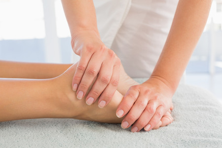 Close-up of a young woman receiving leg massage at spa center photo