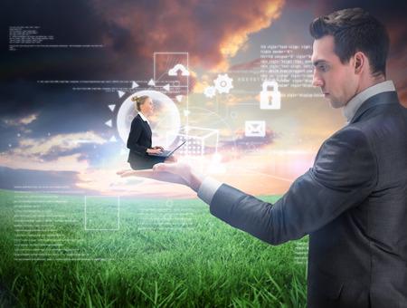 Businesswoman using laptop held by giant businessman against green field under orange sky photo