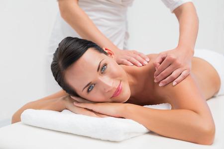 woman massage: Beautiful brunette enjoying a back massage smiling at camera in the health spa