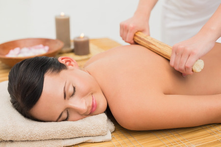 massage table: Beautiful brunette enjoying a bamboo roller massage in the health spa Stock Photo