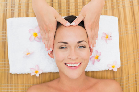 Smiling brunette enjoying a head massage in the health spa photo