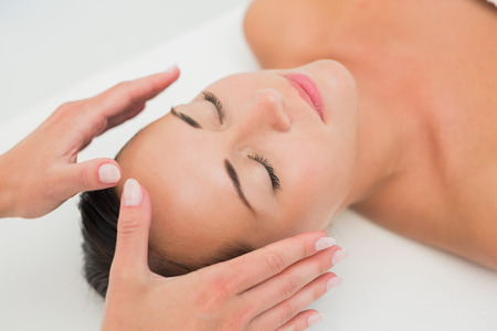 chakra healing: Peaceful brunette getting reiki therapy in the health spa