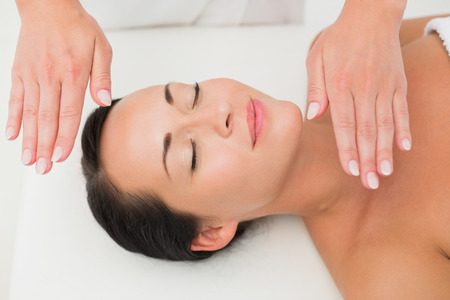 Peaceful brunette getting reiki therapy in the health spa photo