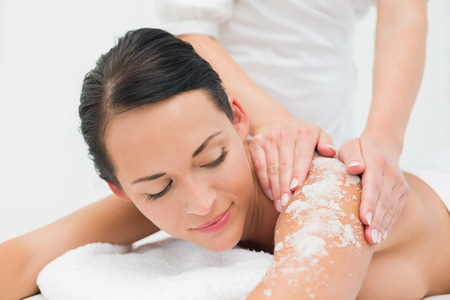 women body: Peaceful brunette getting a salt scrub beauty treatment in the health spa Stock Photo