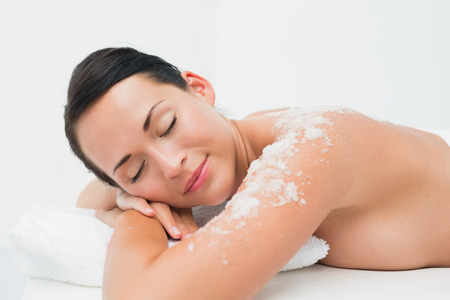 Peaceful brunette lying with salt scrub on shoulders in the health spa photo