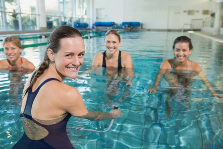 swimming pool woman: Female fitness class doing aqua aerobics on exercise bikes in swimming pool at the leisure centre