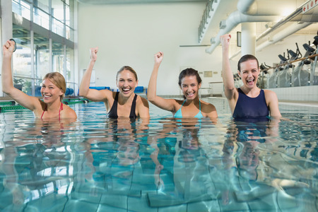 Female fitness class doing aqua aerobics and cheering in swimming pool at the leisure centre Stock Photo