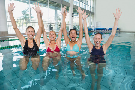 Female fitness class doing aqua aerobics and cheering in swimming pool at the leisure centre Фото со стока
