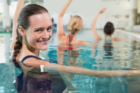 Female fitness class doing aqua aerobics in swimming pool at the leisure centre photo