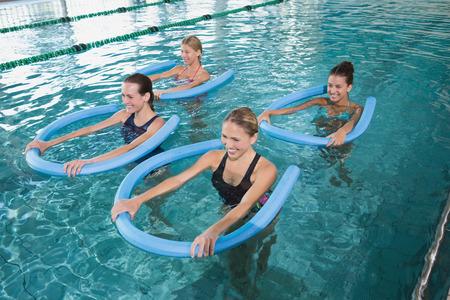 레저 센터 수영장에서 폼 롤러와 아쿠아 에어로빅 피트니스 클래스 스톡 콘텐츠