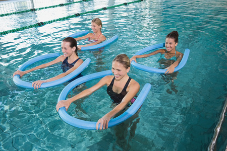 water aerobics: Fitness class doing aqua aerobics with foam rollers in swimming pool at the leisure centre