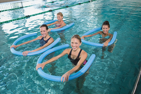 swimming pool float: Fitness class doing aqua aerobics with foam rollers in swimming pool at the leisure centre