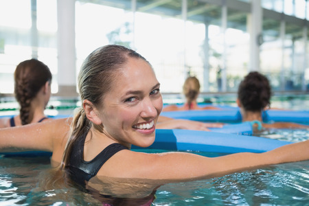 Happy fitness class doing aqua aerobics with foam rollers in\ swimming pool at the leisure centre