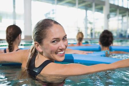 Happy Fitness-Klasse macht Aqua-Aerobic mit Schaumrollen in Swimmingpool im Freizeitzentrum Standard-Bild - 30959315