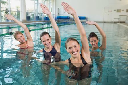 레저 센터에서 수영장에서 아쿠아 에어로빅을하는 여성 피트니스 클래스 미소