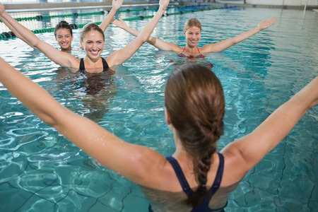 Smiling female fitness class doing aqua aerobics in swimming pool at the leisure centre photo