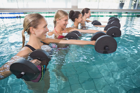Smiling female fitness class doing aqua aerobics with foam dumbbells in swimming pool at the leisure centre photo