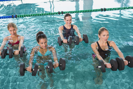 water aerobics: Female fitness class doing aqua aerobics with foam dumbbells in swimming pool at the leisure centre