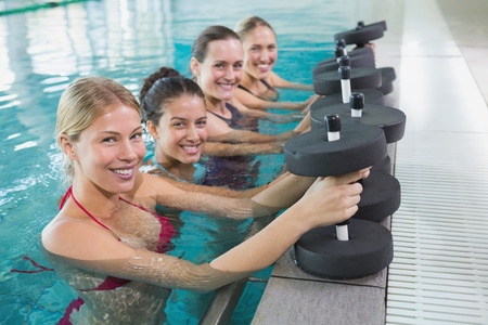Female fitness class doing aqua aerobics with foam dumbbells in swimming pool at the leisure centre photo