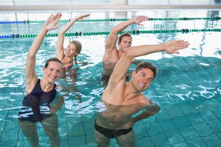 Happy Fitness-Klasse tut Aqua-Aerobic im Schwimmbad im Freizeitzentrum Standard-Bild - 30959342