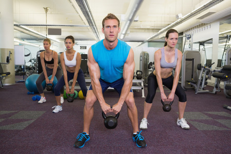 Muscular instructor leading kettlebell class at the gym photo
