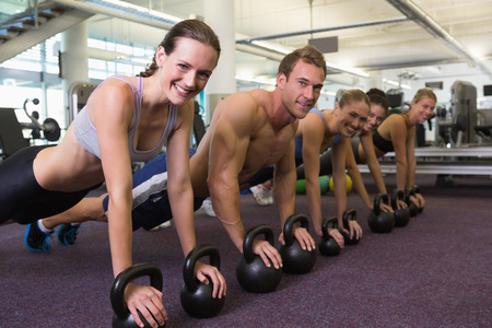 Fitness class in plank position with kettlebells at the gym photo