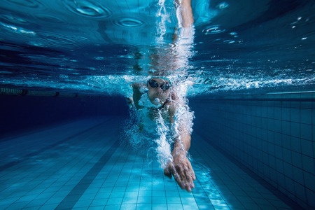 swimming goggles: Fit swimmer training by himself in the swimming pool at the leisure centre