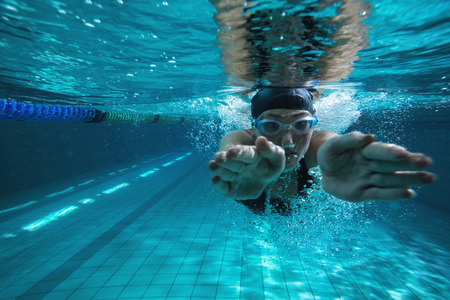 swimming: Athletic swimmer training on her own in the swimming pool at the leisure centre