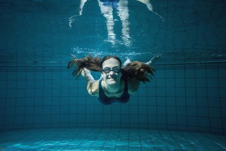 Athletisch Schwimmer lächelnd in die Kamera unter Wasser im Schwimmbad im Freizeitzentrum