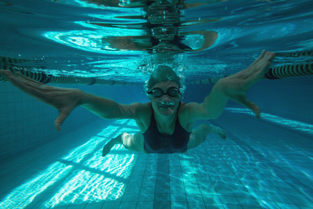 Athletic swimmer swimming towards camera in the swimming pool\ at the leisure centre