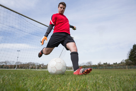 Goalkeeper in red kicking ball away from goal on a clear day photo