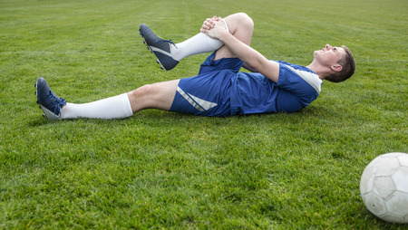 Football player in blue lying injured on the pitch on a clear day photo