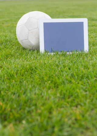 Football and tablet with blank screen on pitch on a clear day photo