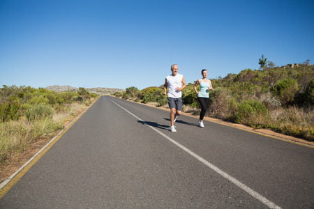 fit couple: Fit couple running on the open road together on a sunny day Stock Photo