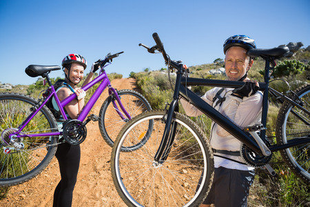 mid adult couples: Active couple carrying their bikes on country terrain together on a sunny day Stock Photo