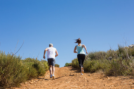adventuring: Fit couple jogging up mountain trail on a sunny day Stock Photo