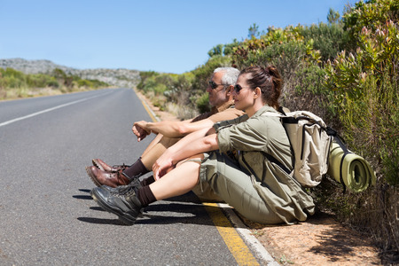 Hiking couple sitting on the side of the road on a sunny day photo
