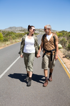 Hitch hiking couple holding hands on the road on a sunny day photo