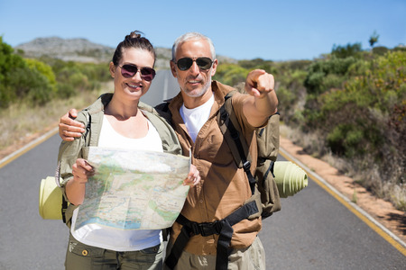 Hiking couple looking at map on the road on a sunny day photo