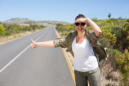 hitch hiker: Pretty hitchhiker sticking thumb out on the road on a sunny day
