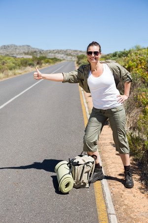 Pretty hitchhiker sticking thumb out on the road on a sunny day photo