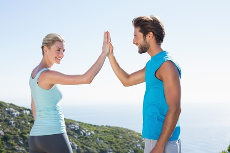 fit couple: Fit couple standing high fiving on a sunny day