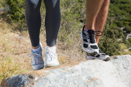 fit couple: Fit couple jogging up mountain trail on a sunny day Stock Photo