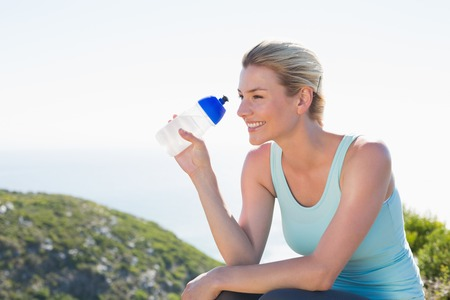 Fit blonde sitting at summit holding water bottle on a sunny day Stock Photo